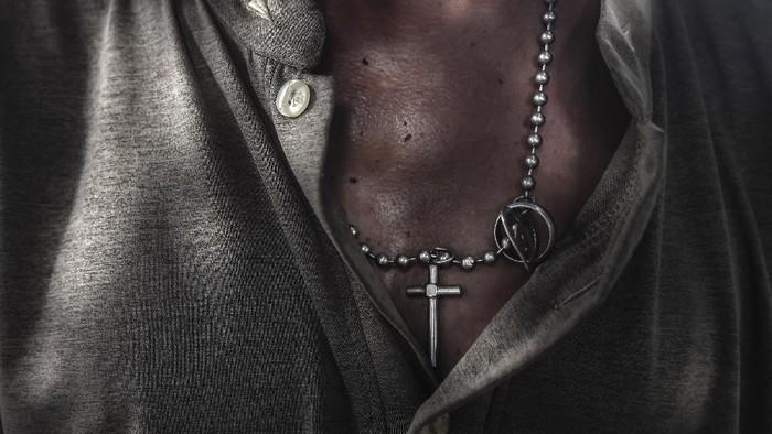 Kalung salib berbahan logam melingkar di leher Salomon.