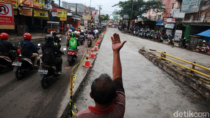 Pengendara melintasi proyek peninggian jalan untuk penanganan banjir di Jl KH Hasyim Ashari, Ciledug, Kota Tangerang, Kamis (3/12/2020). Proyek tersebut berdampak pada penyempitan jalan dan kemacetan. Kepadatan lalu-lintas hingga 800an meter di kedua arah tergantung jam sibuk lalu-lintas. Jalan ini merupakan salah satu akses dari Kota Tangerang ke Jakarta.