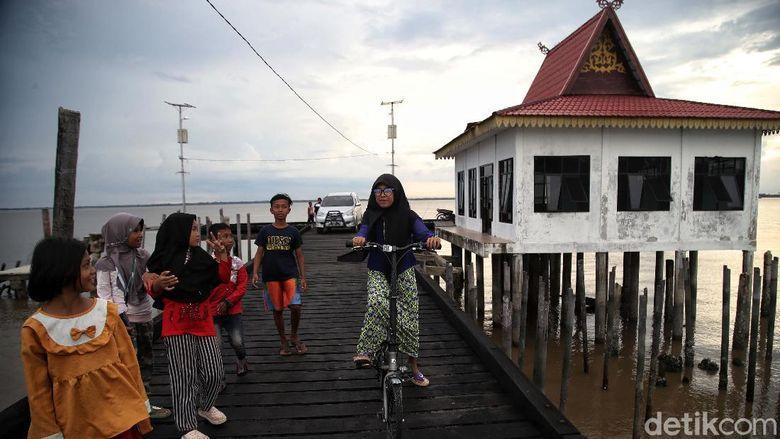 Sejumlah warga beraktivitas di kawasan Dermaga Batu Panjang, Rupat Selatan, Bengkalis, Riau, Rabu (18/11). Menurut keterangan warga, dermaga tersebut telah rusak sejak beberapa tahun terakhir karena kurangnya perawatan dan ketidakpedulian pemkab dan warga sekitar.