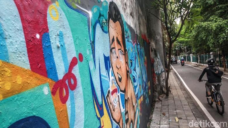 Warga melintas di depan grafiti Tumbang di kawasan Cikini, Jakpus. Tulisan Tumbang dilengkapi mural karakter pria mengenakan baju coklat dengan nametag DKI-1.