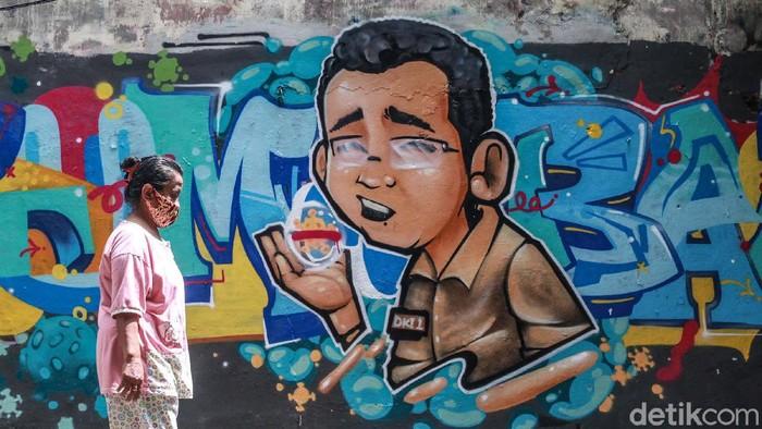 Warga melintas di depan grafiti 'Tumbang' di kawasan Cikini, Jakpus. Tulisan 'Tumbang' dilengkapi mural karakter pria mengenakan baju coklat dengan nametag 'DKI-1'.