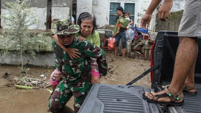 Prajurit TNI bersama sejumlah relawan mengevakuasi warga terdampak banjir di kawasan Medan. Diketahui banjir rendam Medan dan menyebabkan ribuan warga mengungsi