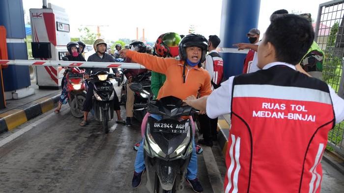 Pengendara sepeda motor memaksa masuk ke gerbang tol Semayang di Deli Serdang, Sumatera Utara, Jumat (4/12/2020). Ratusan pengendara sepeda motor dari arah Kabupaten Deli Serdang menuju Kota Medan menerobos dan melawan petugas jalan tol dikarenakan jalan utama penghuhung dua daerah tersebut terendam banjir. ANTARA FOTO/Irsan Mulyadi/Lmo/foc.