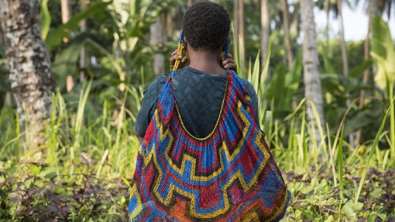 Seorang perempuan PNG menggendong anaknya yang berumur 6 bulan dengan bilum di Desa Kudk, Pulau Karkar, Provinsi Madang, Papua new Guinea. Bilum adalah tas tradisional PNG.