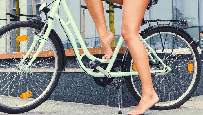 Womans tan legs riding a bicycle over modern building background.