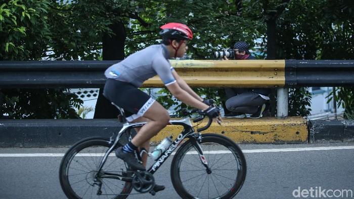 Penasaran kenapa foto para pesepeda keren-keren? Ini dia sosok-sosok fotografer yang rela rebahan di jalan hingga ngumpet di semak-semak dan pembatas jalan.
