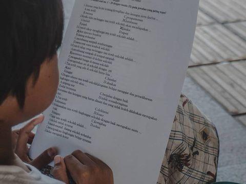 Bocah pemulung memegang secarik kertas tugas