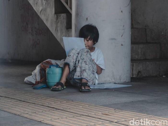 Bocah pemulung mengerjakan tugas di trotoar Kota Bandung