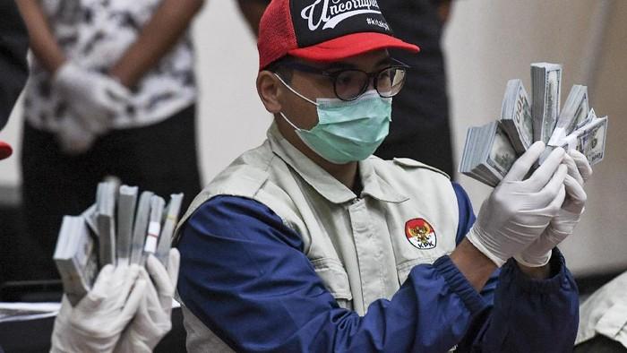 Penyidik KPK menunjukan barang bukti uang tunai saat konferensi pers terkait Operasi Tangkap Tangan (OTT) tindak pidana korupsi pada program bantuan sosial di Kementerian Sosial untuk penanganan COVID-19 di Gedung KPK, Jakarta, Minggu (6/12/2020) dini hari. Dalam operasi tangkap tangan itu KPK menetapkan lima tersangka yakni Menteri Sosial Juliari P Batubara, pejabat pembuat komitmen di Kemensos Matheus Joko Santoso dan Adi Wahyono dan pihak swasta Ardian IM dan Harry Sidabuke  serta mengamankan uang dengan jumlah Rp14,5 miliar. ANTARA FOTO/Hafidz Mubarak A/rwa.