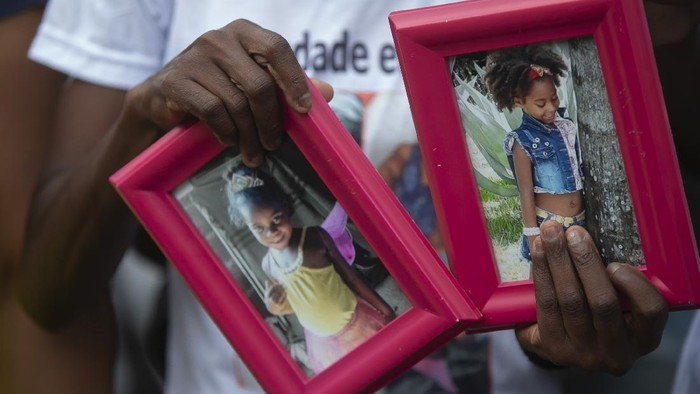 Ana Lucia Silva Moreira, 38, mother of Emily Victoria Silva dos Santos, 4, and aunt of Rebeca Beatriz Rodrigues dos Santos, 7, holds photos of the two girls during a protest in Duque de Caxias, Rio de Janeiro state, Brazil, Sunday, Dec. 6, 2020. Emily Victoria Silva dos Santos and Rebeca Beatriz Rodrigues dos Santos, were killed by stray bullets while playing outside their homes. (AP Photo/Bruna Prado)