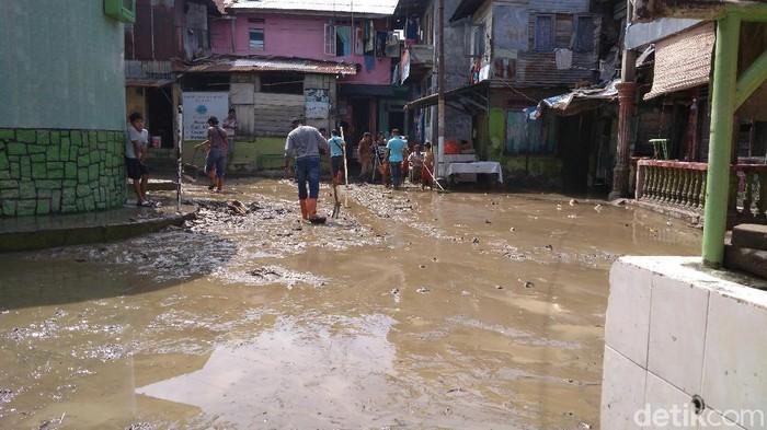 Warga keruk lumpur pascabanjir di Medan.