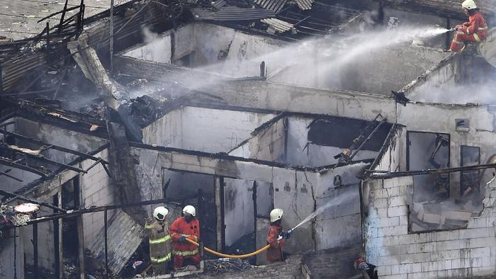 Petugas pemadam kebakaran mendinginkan sisa bangunan yang terbakar di kawasan Bendungan Hilir, Jakarta Pusat, Selasa (8/12/2020). Sebanyak 12 unit mobil pemadam kebakaran dari Suku Dinas Penanggulangan Kebakaran dan Penyelamatan Jakarta Pusat dikerahkan untuk memadamkan api yang membakar hunian di permukiman tersebut. ANTARA FOTO/Sigid Kurniawan/rwa.