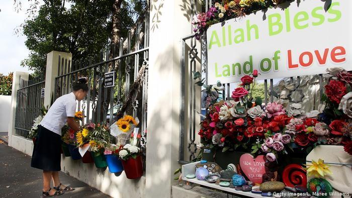 Seorang perempuan meletakan bunga di depan pintu masuk Masjid An-Nur di Christchurch, Selandia Baru.