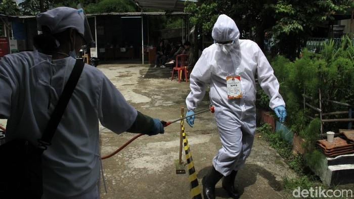 Petugas yang mengenakan APD dibersikan dengan cairan disinfektan oleh rekannya seusai berkeliling ke rumah warga yang mengalami isolasi, sakit dan juga lansia dalam penyelenggaraan Pilkada Kota Depok, Jawa Barat