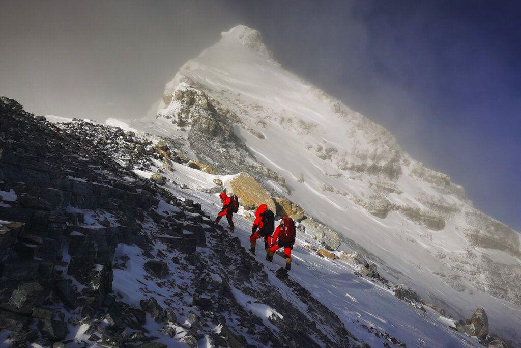 Foto ini dirilis Xinhua News Agency pada bulan Mei 2020: salah satu anggota tim survei China memasang peralatan di Gunung Everest yang oleh warga lokal dinamai Gunung  Qomolangma. China dan Nepal mengumumkan ketinggian baru Gunung Everest pada 8 Desember  2020 (Tashi Tsering/Xinhua via AP, File)