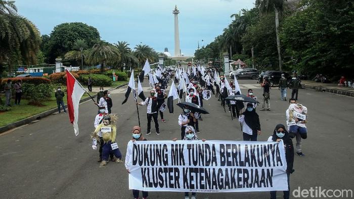 Sejumlah buruh gelar aksi di kawasan Monas, Jakarta. Mereka mendesak MK untuk melanjutkan sidang uji materi UU Cipta Kerja yang tertunda gegara virus Corona.