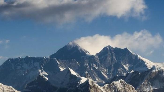 Anggota staf Departemen Survei menghadiri pengumuman virtual soal ketinggian Gunung Everest di Kathmandu pada 8 Desember 2020. Keputusan itu mengakhiri debat selama beberapa dekade dengan diputuskan ketingguan Gunung Everest kini 8.848.86 mdpl atau 86 cm lebih tinggi ketimbang yang ditetapkan Nepal sebelumnya atau 4 meter di bawah pengakuan resmi China sebelumnya. (Photo by PRAKASH MATHEMA / AFP)