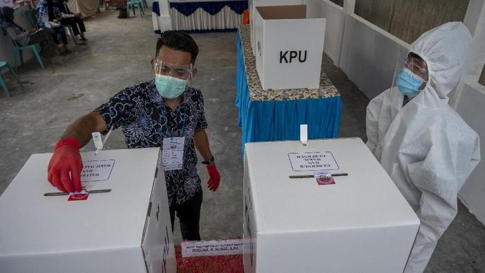 Petugas KPPS mengenakan alat pilindung diri saat bertugas pada Pilkada Serentak di TPS 08, Kelurahan Palupi, Palu, Sulawesi Tengah, Rabu (9/12/2020). Penerapan protokol kesehatan dengan 3M, yaitu mencuci tangan, menjaga jarak dan mengenakan masker diwajibkan pada Pilkada Serentak kali ini untuk menghindari penularan COVID-19. ANTARA FOTO/Basri Marzuki/wsj.