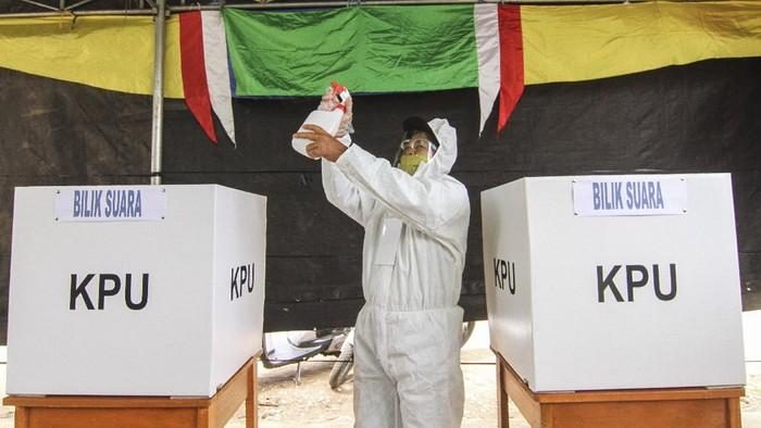 Petugas KPPS berpakaian baju hazmat dan alat pelindung diri (APD) menyemprotkan cairan disinfektan di Tempat Pemungutan Suara (TPS) 13, Cipayung, Depok, Jawa Barat, Rabu (9/12/2020). TPS di Kota Depok menerapkan protokol kesehatan pada Pilkada Serentak 2020 di masa Pandemi COVID-19. ANTARA FOTO/Asprilla Dwi Adha/wsj.