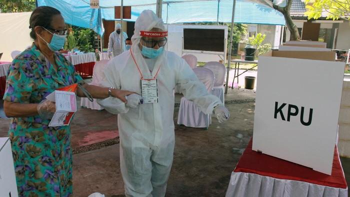 Petugas Kelompok Penyelenggara Pemungutan Suara (KPPS) berpakaian hazmat membantu pemilih menggunakan hak pilihnya di TPS 46 Paku Jaya, Serpong Utara, Tangerang Selatan, Banten, Rabu (9/12/2020). Penggunaan alat pelindung diri (APD) lengkap tersebut untuk meyakinkan masyarakat menggunakan hak pilihnya pada Pilkada Tangerang Selatan 2020 meski di tengah pandemi COVID-19. ANTARA FOTO/Muhammad Iqbal/wsj.