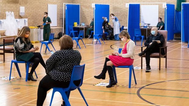 CARDIFF, WALES - DECEMBER 08: People wait after receiving COVID-19 vaccines at Cardiff and Vale Therapy Centre on December 8, 2020 in Cardiff, Wales. More than 50 hospitals across United Kingdom were designated as covid-19 vaccine hubs, the first stage of what will be a lengthy vaccination campaign. NHS staff, over-80s, and care home residents will be among the first to receive the Pfizer/BioNTech vaccine, which recently received emergency approval from the country's health authorities. (Photo by Matthew Horwood/Getty Images)