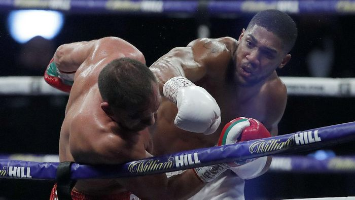 World Heavyweight boxing champion Britains Anthony Joshua lands a blow on challenger Bulgarias Kubrat Pulev during their Heavyweight title fight at Wembley Arena in London Saturday, Dec. 12, 2020. (Andrew Couldridge/Pool via AP)