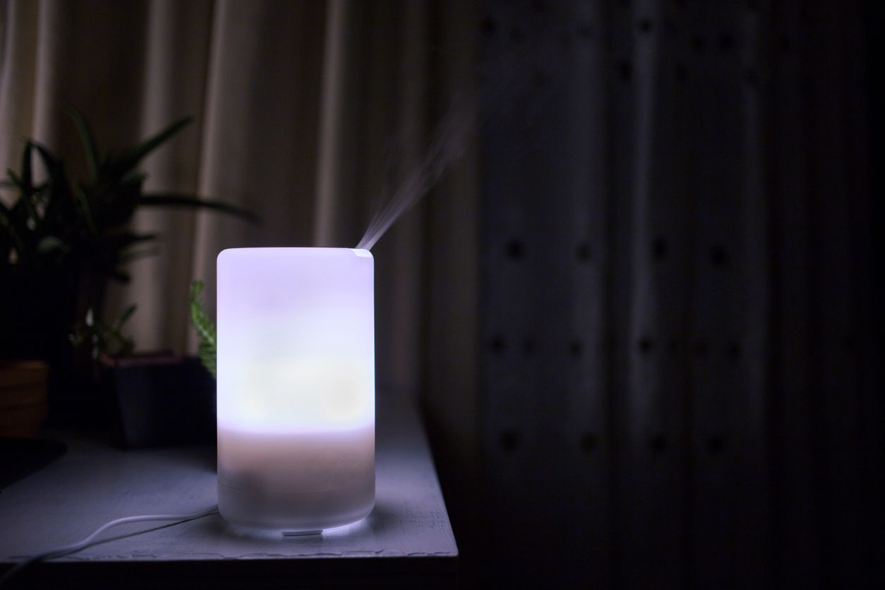 Essential oils diffuser glowing in the dark while diffusing aromatherapy mist