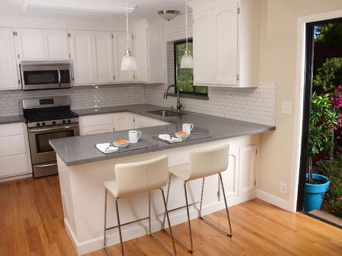 a small modern kitchen with grey cabinets and stainless steel appliances and a decorative bowl.