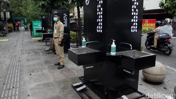 Petugas berjaga di sekitar area tempat cuci tangan.