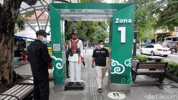 Petugas memantau warga yang melintas di gerbang detektor suhu.