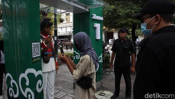 Petugas Jogoboro berjaga dan memberikan arahan kepada wisatawan di depan Gerbang detektor suhu tubuh yang terpasang di jalur pedestrian Malioboro, Yogyakarta, Senin (14/12/2020).