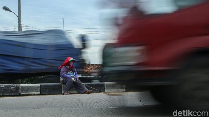 Kehadiran gerombolan orang membawa sapu jadi pemandangan umum saat melintasi Jembatan Sewo, Indramayu. Di sana mereka kumpulkan koin yang dilempar pengendara.