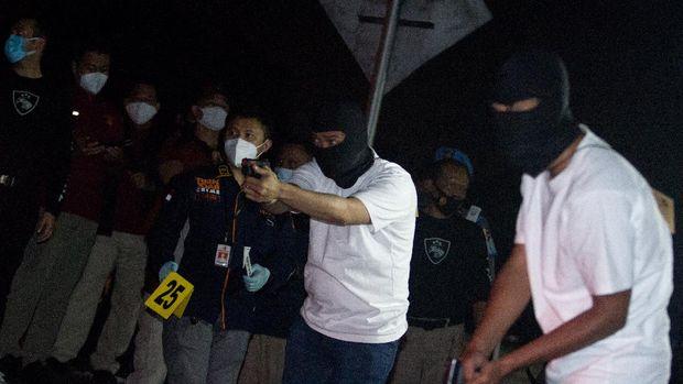 Anggota tim penyidik Bareskrim Polri memperagakan adegan saat rekonstruksi kasus penembakan enam anggota laskar Front Pembela Islam (FPI) di Karawang, Jawa Barat, Senin (14/12/2020) dini hari. Rekonstruksi tersebut memperagakan 58 adegan kasus penembakan enam anggota laskar FPI di tol Jakarta - Cikampek KM 50 pada Senin (7/12/2020) di empat titik kejadian perkara. ANTARA FOTO/M Ibnu Chazar/aww.