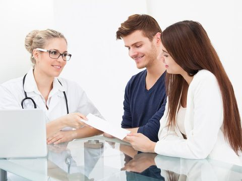 Female doctor giving prescription paper to couple at desk in clinic