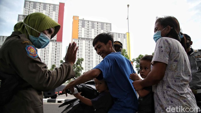 Petugas Satpol PP melakukan operasi tertib masker di kawasan depan Rumah Sakit Darurat COVID-19 Wisma Atlet Kemayoran, Jakarta Pusat, Selasa (15/19).