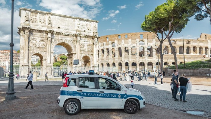 Rome, Italy - October 3, 2019: a police car in front of the Arch of Constantine near the Colosseum or Coliseum.