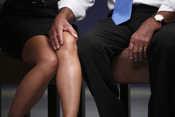 Senior businessman puting his arm on her secretarys knee.
