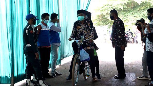 Bapak antar anak wisuda drive thru naik sepeda ontel di Institut Agama Islam Negeri (IAIN) Pekalongan, Jawa Tengah, Selasa (15/12/2020).