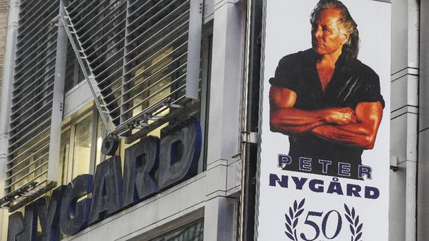 A sign bearing the likeness of Peter Nygard is displayed outside his Times Square headquarters, Tuesday, Feb. 25, 2020, in New York. Federal authorities on Tuesday, Feb. 25, 2020, raided the Manhattan headquarters of the Canadian fashion mogul Peter Nygard amid claims that he sexually assaulted and trafficked dozens of teenage girls and young women. (AP Photo/John Minchillo)
