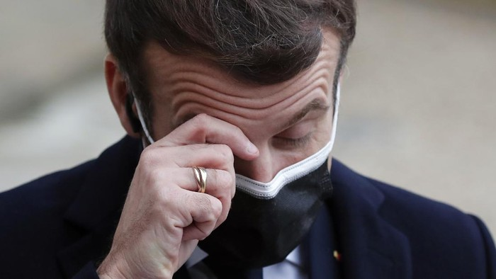 French President Emmanuel Macron reacts as he listen to the speech of Portuguese Prime Minister Antonio Costa, Wednesday, Dec. 16, 2020 in Paris. French President Emmanuel Macron has tested positive for COVID-19, the presidential Elysee Palace announced on Thursday. (AP Photo/Francois Mori)