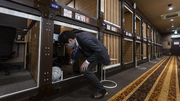 Seorang petugas menunjukkan cara masuk ke dalam coworking space yang sebelumnya adalah kamar hotel kapsul.