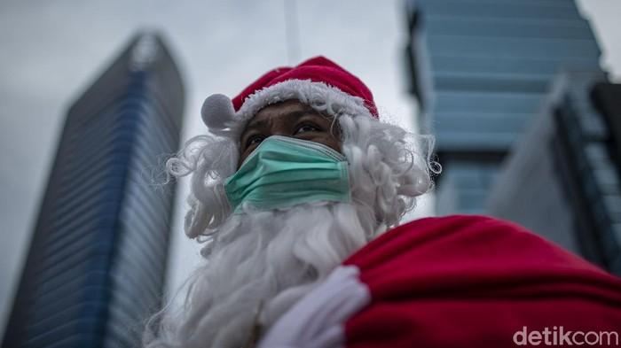 Menyambut perayaan Natal, seorang warga mengenakan baju santa membagikan kopi gratis di jalanan Ibu Kota. Ada beragam jenis kopi yang dibagikannya kepada warga.