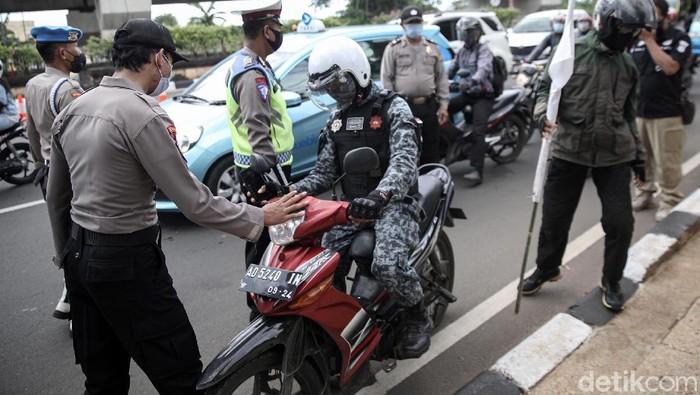 Polisi menghadang massa yang akan ikut aksi 1812 di Pasar Jumat, Jakarta Selatan. Mereka diminta putar balik dan pulang ke rumah.