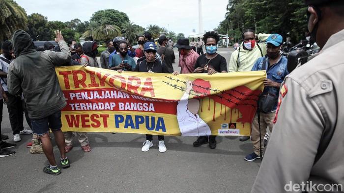 Masyarakat Papua melakukan aksi memperingati operasi Trikora 19 Desember 1961 di Patung Kuda, Medan Merdeka Barat, Jakarta, Sabtu (19/12/2020). Dalam aksi tersebut mereka menuntut 15 isu besar salah satunya Hentikan segala bentuk diskriminasi dan intimidasi terhadap mahasiswa Papua Barat di Indonesia dan Hentikan rasialisme dan politik rasial.