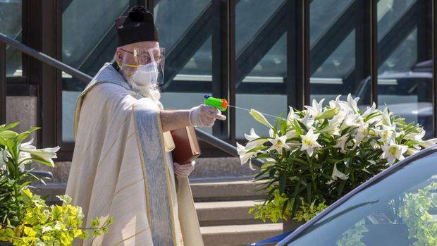 Seorang pastor Katolik Roma di AS menjaga jarak dengan menggunakan pistol air untuk memberkati jemaahnya dengan air suci.