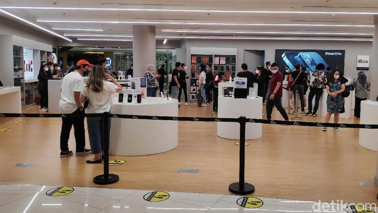 Warga mengantre untuk masuk ke Tenant Ibox kawasan Mall Senayan City, Jakarta Selatan, Sabtu (19/12). Sejak rilis penjualan perdana IPhone 12 di Indonesia pada Jumat kemarin (18/12), tampak di hari kedua ini pengunjung cenderung cukup ramai untuk melihat dan membeli IPhone 12.