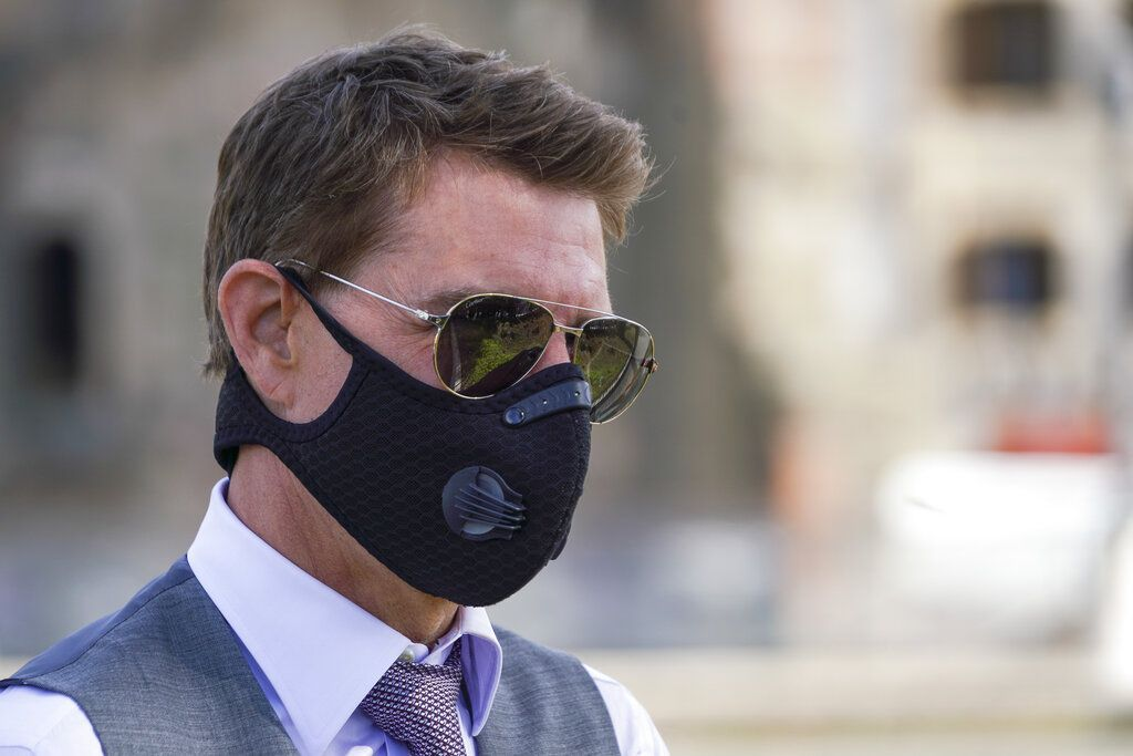 FILE - In this Tuesday, Oct. 13, 2020 file photo, actor Tom Cruise wears a face mask to prevent the spread of COVID-19 as he greets fans during a break from shooting Mission Impossible 7, along Rome's Fori Imperiali avenue. Tom Cruise has launched an expletive-laden rant at colleagues on the set of his latest