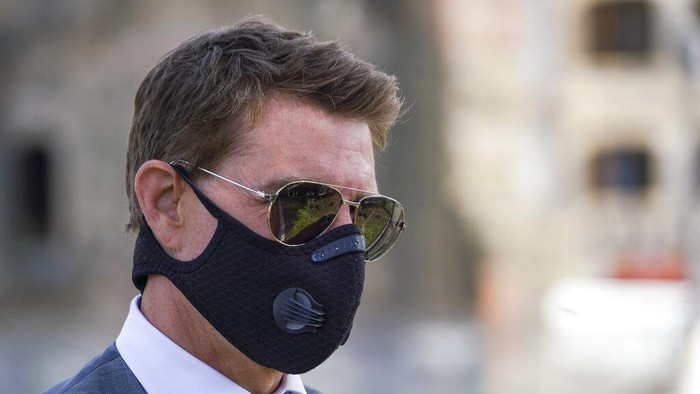 """FILE - In this Tuesday, Oct. 13, 2020 file photo, actor Tom Cruise wears a face mask to prevent the spread of COVID-19 as he greets fans during a break from shooting Mission Impossible 7, along Romes Fori Imperiali avenue. Tom Cruise has launched an expletive-laden rant at colleagues on the set of his latest """"Mission: Impossible"""" movie after he reportedly spotted two workers failing to abide by social distancing rules. In audio released Wednesday, Dec. 16 by the Sun tabloid, the 58-year-old Hollywood megastar can be heard warning that anyone caught not following the rules to stay at least 2 meters (more than 6.5 feet) away from others will be fired. (AP Photo/Andrew Medichini, file)"""