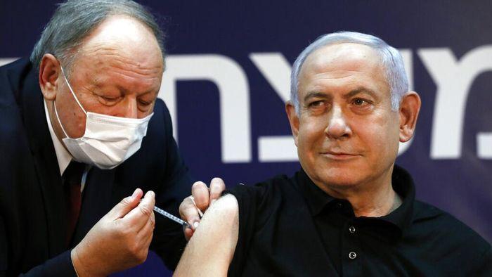 PM Israel Benjamin Netanyahu disuntik vaksin Pfizer-BioNTech. Ia dan Menteri Kesehatan Israel diketahu jadi yang pertama disuntik vaksin COVID-19 di negara itu.