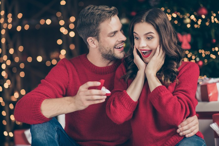 Photo of couple in decorated garland lights room guy giving lady unexpected, engage ring box waiting answer sitting cozy near x-mas tree indoors wear red sweaters